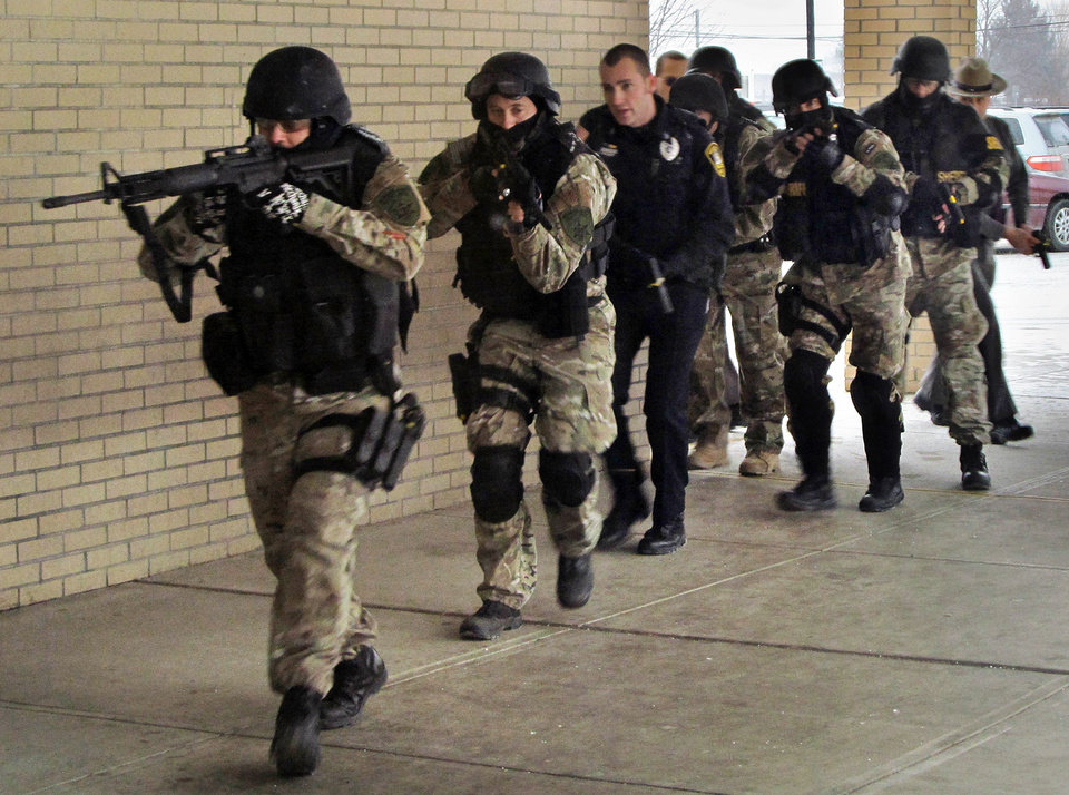 FILE -  In this file photo of Jan. 28, 2013, members of the Washington County Sheriff's Office, the New York State Police and Hudson Falls Police Department approach the entrance to the Hudson Falls Primary School in Hudson Fall, N.Y., to practice drills with unloaded guns to prepare for the possibility of armed intruders at the school. School security has come under more scrutiny in the wake of the Sandy Hook Elementary School massacre in Newtown, Conn., that killed 26 people in December. (AP Photo/The Post-Star, Omar Ricardo Aquije, File)