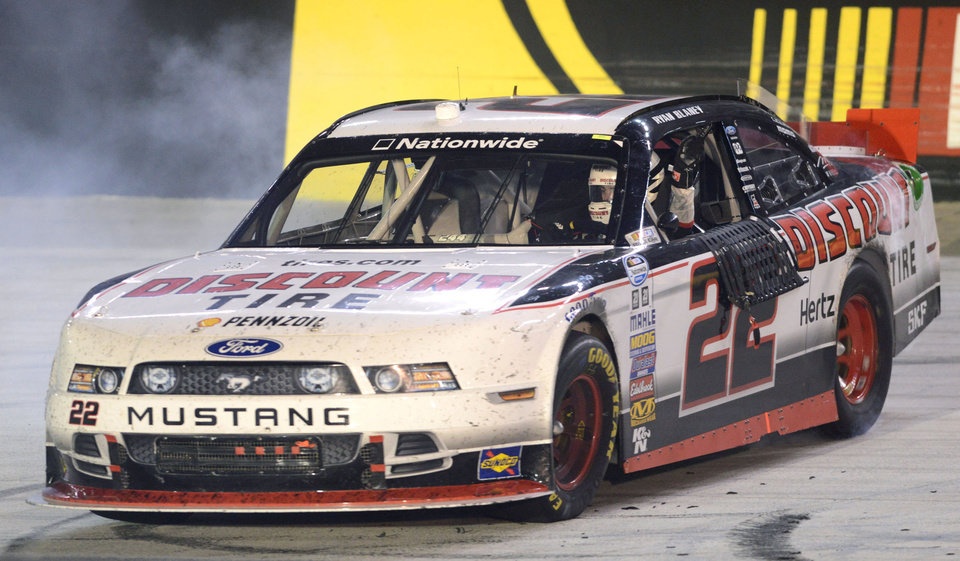 Photo - Ryan Blaney celebrates his win in the NASCAR Nationwide series auto race with a burnout on the front stretch Friday night, Aug. 22, 2014, at Bristol Motor Speedway in Bistol Tenn. (AP Photo/Bristol Herald Courier, David Crigger)