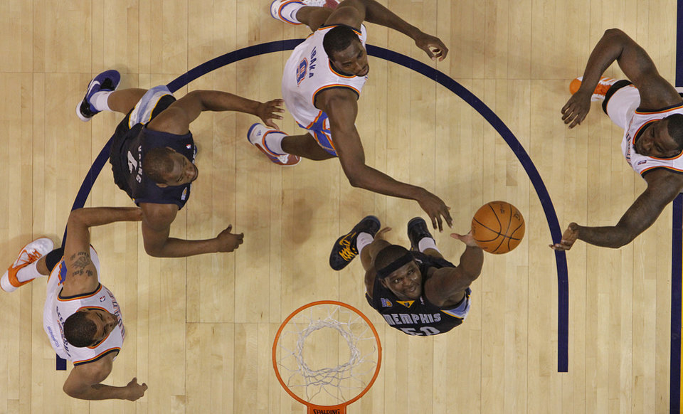 Photo - Memphis' Zach Randolph (50) pulls in a rebound over Oklahoma City's Thabo Sefolosha (2), Serge Ibaka (9) and Kendrick Perkins (5) during game one of the Western Conference semifinals between the Memphis Grizzlies and the Oklahoma City Thunder in the NBA basketball playoffs at Oklahoma City Arena in Oklahoma City, Sunday, May 1, 2011. Photo by Chris Landsberger, The Oklahoman