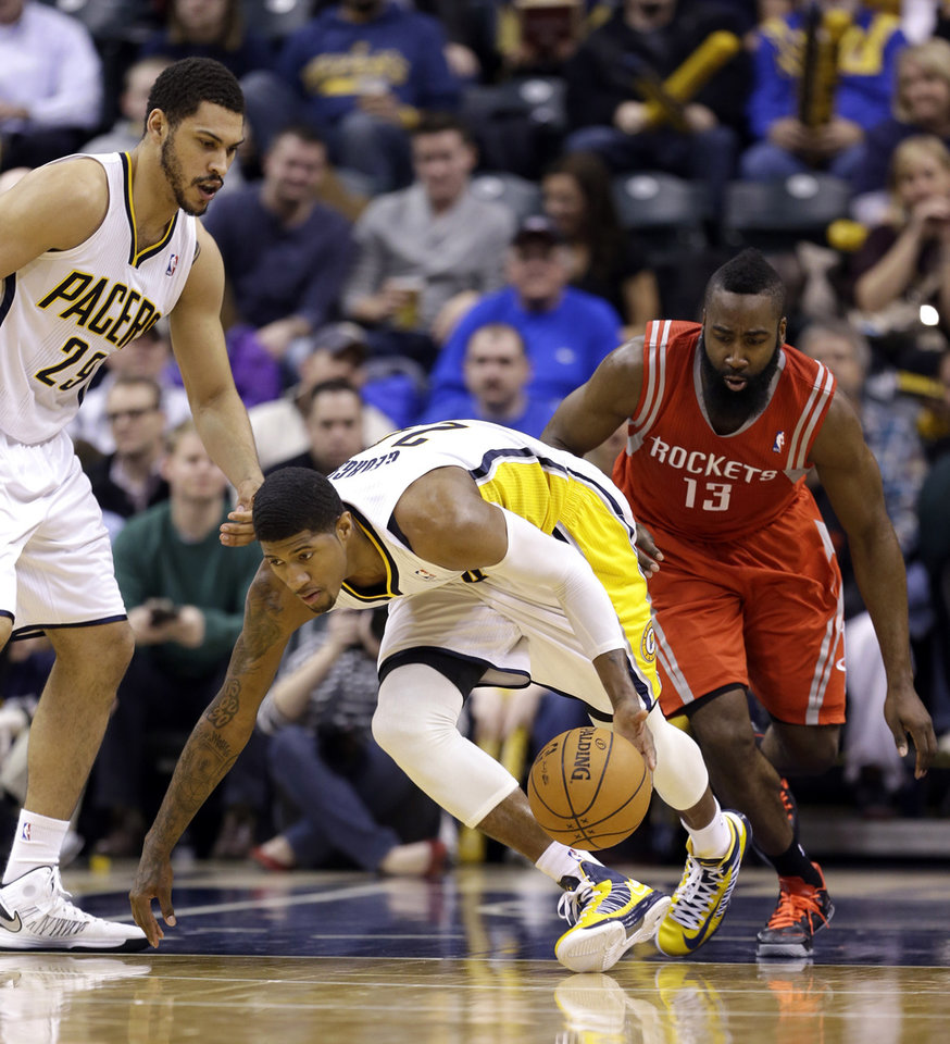 Photo - Indiana Pacers' Paul George (24) makes a steal in front of Jeff Pendergraph, left, and Houston Rockets' James Harden (13) during the second half of an NBA basketball game Friday, Jan. 18, 2013, in Indianapolis. The Pacers defeated the Rockets 104-93. (AP Photo/Darron Cummings)
