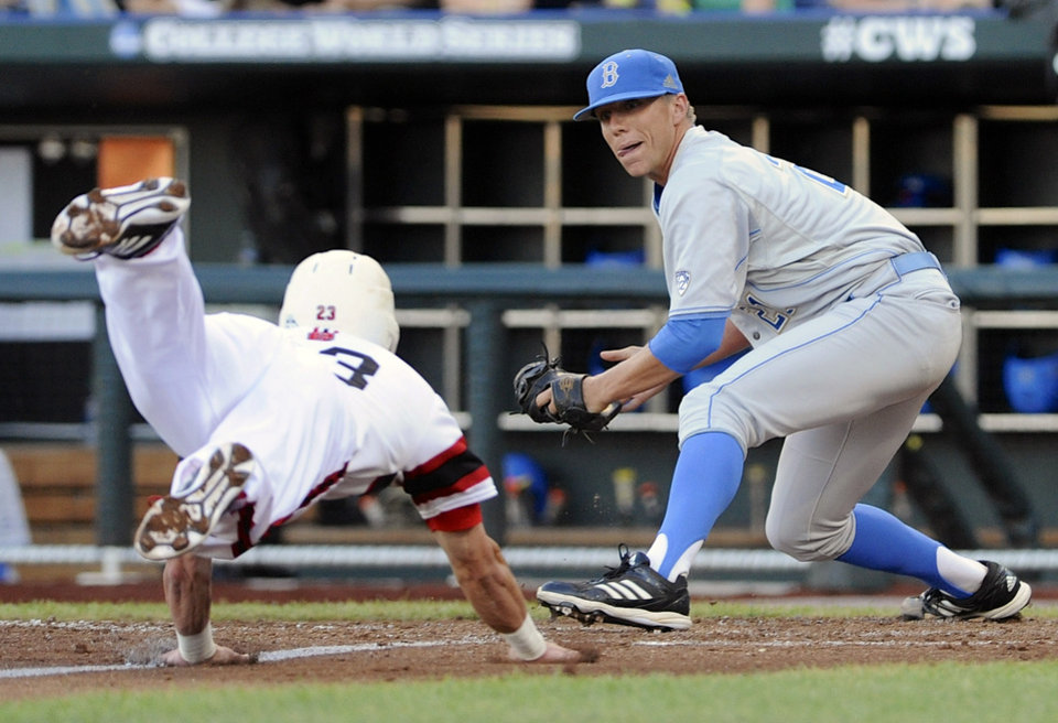 Photo - UCLA pitcher Nick Vander Tuig right, prepares to tag out North Carolina State's Jake Armstrong at home plate on a single by Trea Turner in the third inning of an NCAA College World Series baseball game in Omaha, Neb., Tuesday, June 18, 2013. (AP Photo/Eric Francis)