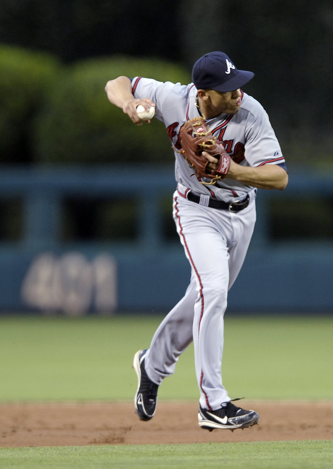 Photo - Atlanta Braves' Andrelton Simmons fields a ball hit by Philadelphia Phillies' Kyle Kendrick and throws him out in the third inning of a baseball game on Saturday, July 6, 2013, in Philadelphia. (AP Photo/Michael Perez)