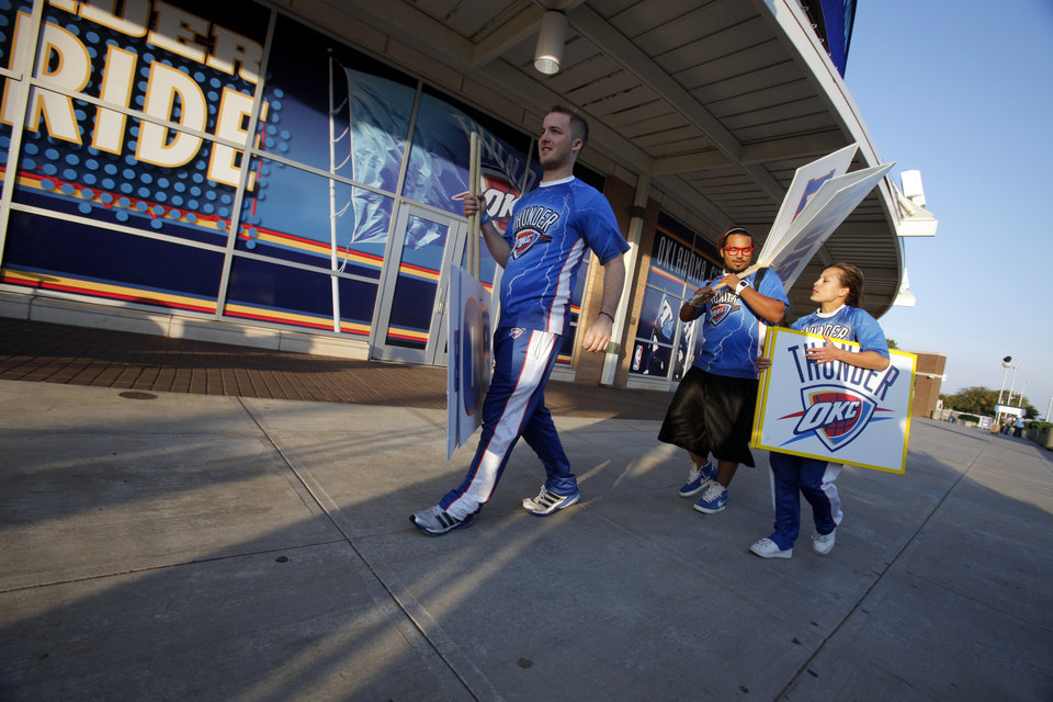 Thunder Storm Chasers Devin Newsom, JoJo McNeal, and Anita Pluto-Elliott walk past the arena at dawn after getting up early to appear on morning news shows on the day the first game of the NBA basketball finals at the Chesapeake Arena on Tuesday, June 12, 2012 in Oklahoma City, Okla.  Photo by Steve Sisney, The Oklahoman