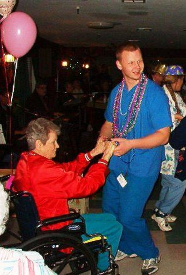 (from left) Grace Living Center - El Reno resident Chey Polk dances with employee Donald Bryant during the annual Mardi Gras celebration at the nursing home.<br/><b>Community Photo By:</b> Angie Bradway<br/><b>Submitted By:</b> Tilford, Oklahoma City