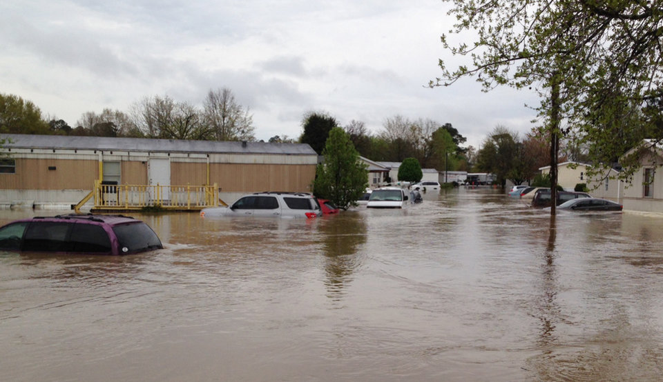 Photo - Flood waters cover a street in a mobile home park in Pelham, Ala., on Monday, April 7, 2014. Police and firefighters rescued about a dozen people who were trapped by muddy, fast-moving water after storms dumped torrential rains in central Alabama. (AP Photo/Jay Reeves)