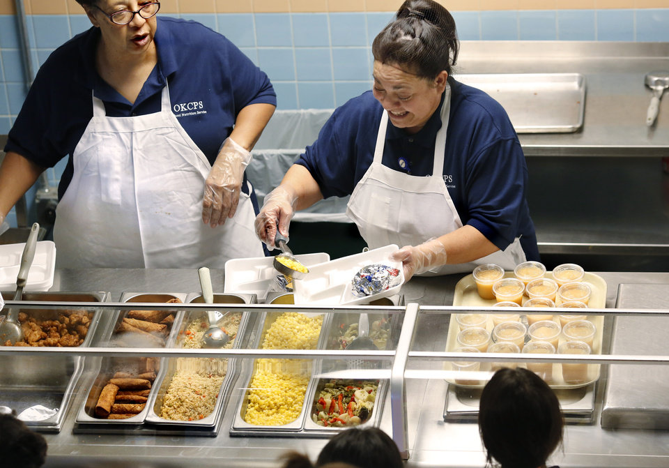 Photo -  Cafeteria workers at Eugene Field Elementary School in Oklahoma City serve lunch Thursday. [Photo by Jim Beckel, The Oklahoman]