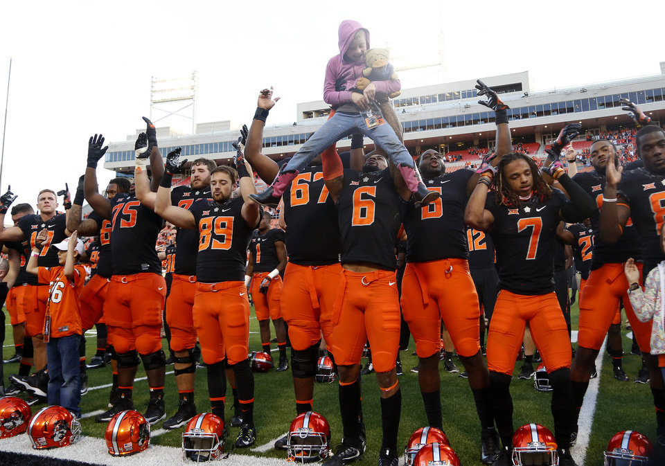 Photo - Oklahoma State's Ashton Lampkin (6) lifts Arleigh Williams in the air following a college football game between the Oklahoma State University Cowboys (OSU) and the Iowa State University at Boone Pickens Stadium in Stillwater, Okla., Saturday, Oct. 8, 2016. Photo by Sarah Phipps, The Oklahoman