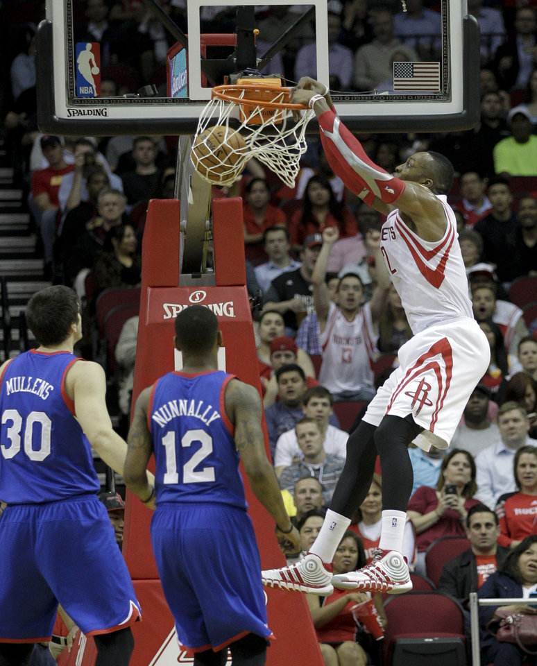 Photo - Houston Rockets' Dwight Howard, right, dunks over Philadelphia 76ers' James Nunnally (12) and Byron Mullens (30) during the first half of an NBA basketball game on Thursday, March 27, 2014, in Houston. (AP Photo/Bob Levey)