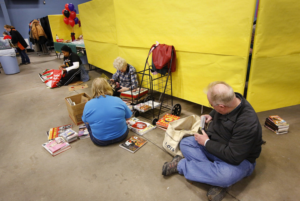 Taking a break from shopping, these people sit on the floor taking a closer look at the items they have selected before getting in the line to make their purchases. through Several thousand bibliophiles and bargain hunters crowded into Oklahoma Expo Hall at State Fair Park on Saturday, Feb. 23, 2013, in a quest to find reading material at deeply discounted prices. Friends of the Metropolitan Library System is holding their much-anticipated annual book sale this weekend. The sale continues Sunday from 9 a.m. to 5:30 p.m. Photo by Jim Beckel, The Oklahoman