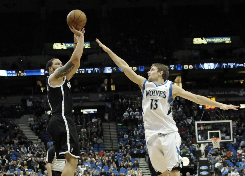 Photo - Minnesota Timberwolves' Luke Ridnour, right, defends as Brooklyn Nets' Deron Williams shoots over him in the second half of an NBA basketball game on Wednesday, Jan. 23, 2013, in Minneapolis. The Nets won 91-83. Williams scored 18 points along with Joe Johnson and Ridnour had 13 points for the Timberwolves. (AP Photo/Jim Mone)