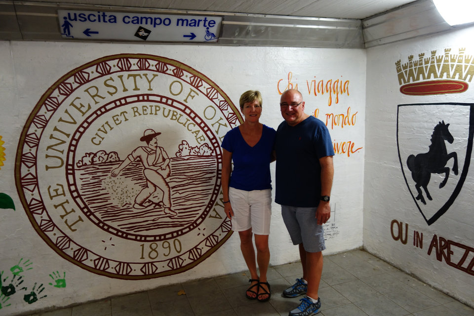 Photo -  Jim Sluss, associate dean of OU's College of Engineering, and his wife, Julie, stand in front of the OU seal which adorns a tunnel wall in the Arezzo train station. (Photo by Berry Tramel)