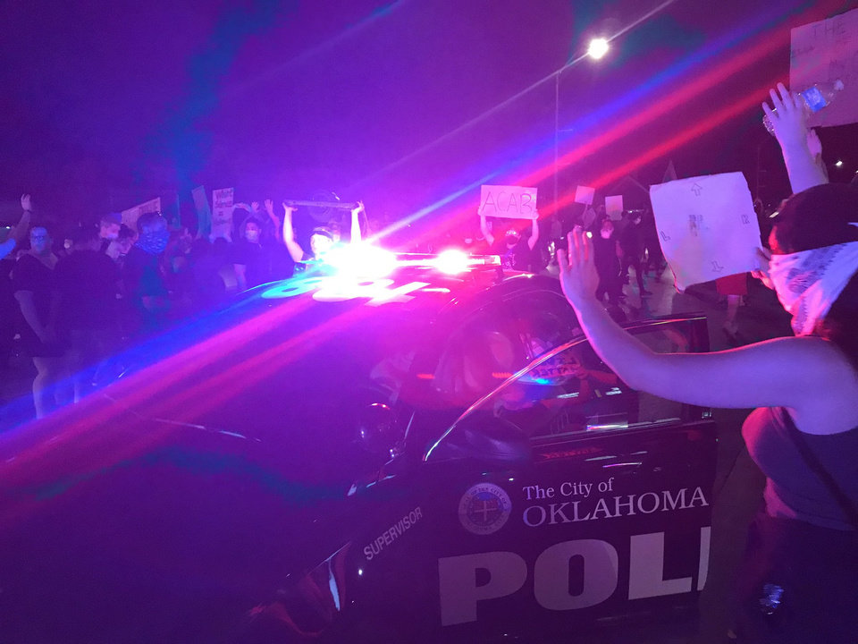 Photo - Oklahoma City Police cars arrive Saturday, May 30, 2020, as protesters walk along NW 23rd in Oklahoma CIty. Photo by Sarah Phipps