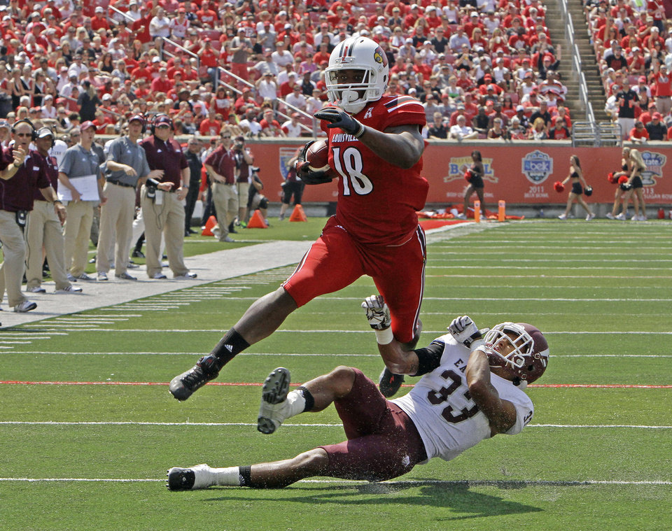 Photo - Louisville tight end Gerald Christian (18) slips away from Eastern Kentucky's Jason Fergerson (33) after making a catch in the second quarter of their NCAA college football game in Louisville, Ky., Saturday, Sept. 7, 2013. The big gain was nullified by a blocking penalty. (AP Photo/Garry Jones)