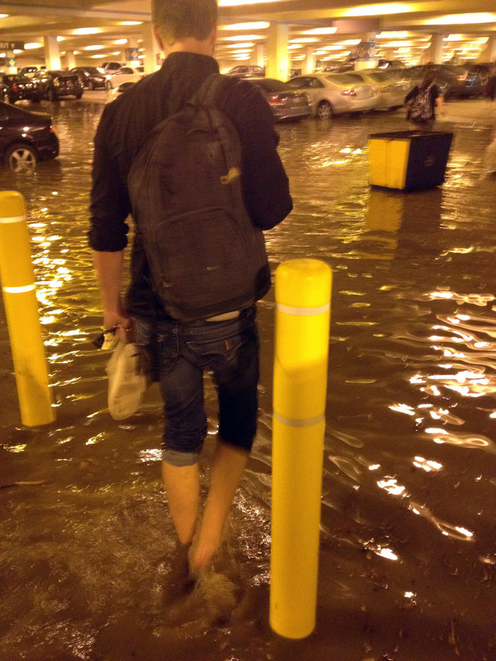 Photo - In this Tuesday, July 29, 2014 photo, a person walks through a flooded parking structure at UCLA after a ruptured 93-year-old, 30-inch water main left the Los Angeles campus awash in 8 million gallons of water in the middle of California's worst drought in decades. The water also flooded the school's storied basketball court, which underwent a major renovation less than two years ago. (AP Photo/Anuj Dixit)