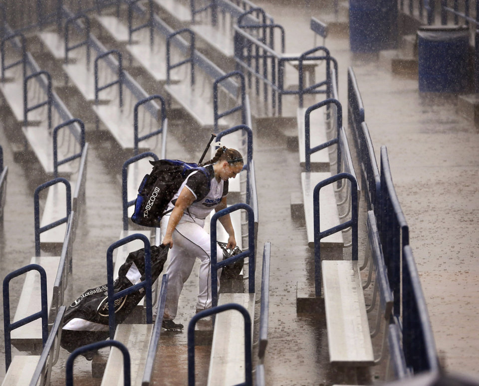 An Oologah softball player carries her equipment up the stadium steps during a heavy downpour as she leaves Hall of Fame Stadium in Oklahoma City after officials announced all scheduled high school softball championship games set to be played there Saturday were canceled due to severe weather, heavy rain and poor field conditions. Class 4A, 5A and 6A softball games have been rescheduled for Monday. Oologah was leading Piedmont in the fourth inning when their game was suspended. Strong thunderstorms, producing heavy downpours and lightning moved through the Oklahoma City area  during the morning and early afternoon hours on Saturday, Oct. 13, 2012. Overcast skies and intermittent rain continued throughout the day.    Photo by Jim Beckel, The Oklahoman