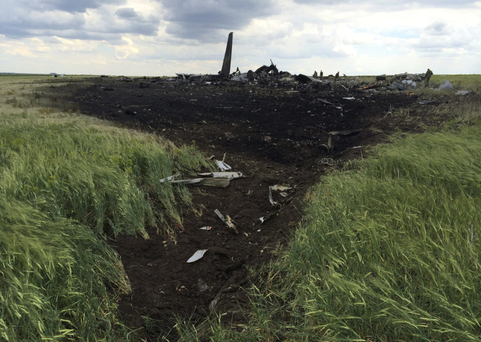 Photo - Remnants of a downed Ukrainian army aircraft Il-76  on the ground at the airport near Luhansk, Ukraine, Saturday, June 14, 2014. Pro-Russian separatists shot down the military transport plane Saturday in the country's restive east, killing all 49 service personnel on board, Ukrainian officials said. (AP Photo/Evgeniy Maloletka)