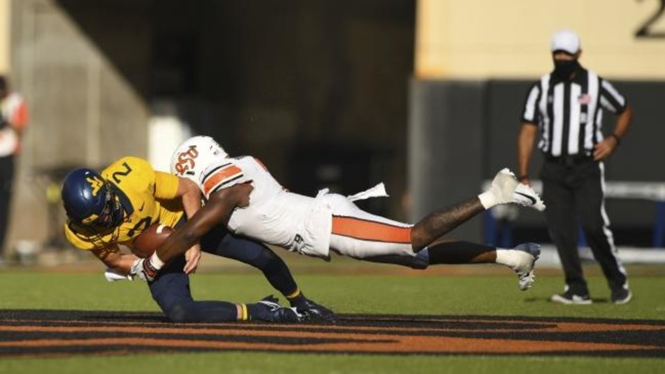 Photo -  Oklahoma State linebacker Amen Ogbongbemiga (7) tackles West Virginia quarterback Jarret Doege (2) during the Cowboys' 27-13 win last Saturday in Stillwater. [AP Photo/Brody Schmidt]