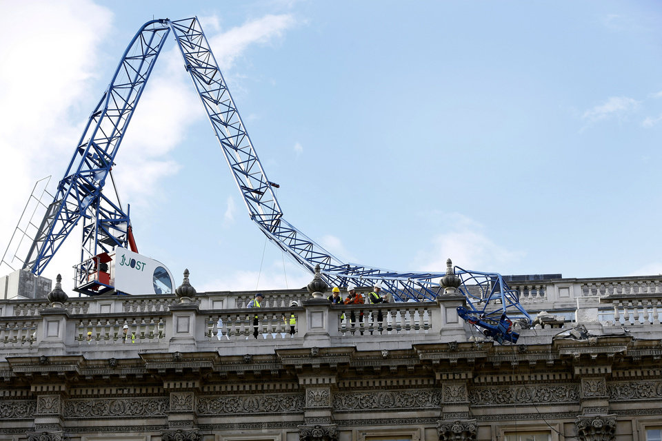 Photo - Workmen survey the damage caused by a crane brought down by high winds onto the roof of the Cabinet Office in Whitehall, near Downing Street in London, Monday, Oct. 28, 2013. A major storm with hurricane-force gusts lashed southern Britain, the Netherlands and parts of France on Monday, knocking down trees, flooding low areas and causing travel chaos. (AP Photo/Kirsty Wigglesworth)