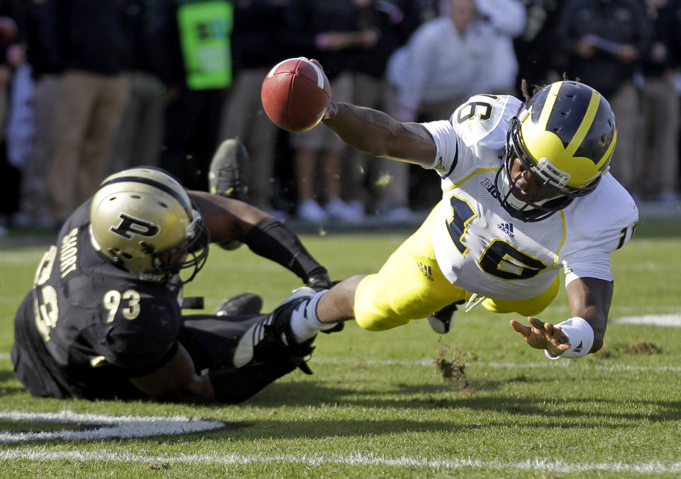 Michigan quarterback Denard Robinson, right, dives to the one-yard line as he's tackled by Purdue defensive tackle Kawann Short during the first half of an NCAA college football game in West Lafayette, Ind., Saturday, Oct. 6, 2012. (AP Photo/Michael Conroy)