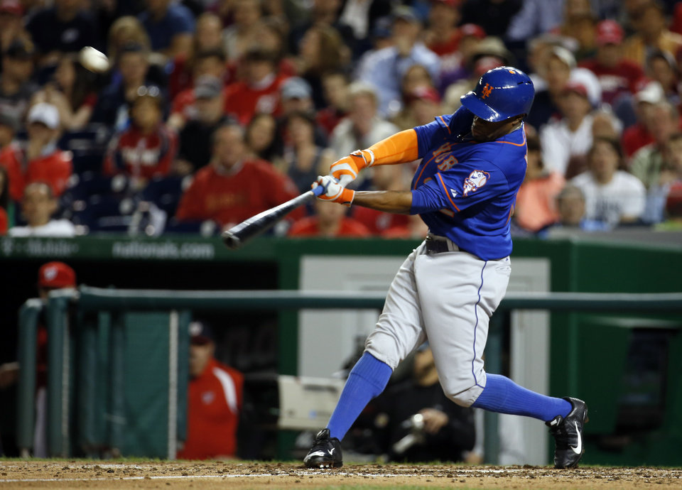 Photo - New York Mets' Eric Young Jr. hits an RBI double during the fifth inning of a baseball game against the Washington Nationals at Nationals Park Friday, May 16, 2014, in Washington. (AP Photo/Alex Brandon)