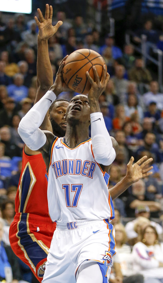 Photo - Oklahoma City's Dennis Schroder (17) shoots in front of New Orleans' Ian Clark (2) during an NBA basketball game between the Oklahoma City Thunder and the New Orleans Pelicans at Chesapeake Energy Arena in Oklahoma City, Monday, Nov. 5, 2018. Photo by Nate Billings, The Oklahoman