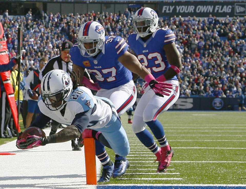 Photo -   Tennessee Titans running back Chris Johnson (28) scores a touchdown in front of Buffalo Bills defenders George Wilson (37) and Aaron Williams (23) during the first half of an NFL football game in Orchard Park, N.Y., Sunday, Oct. 21, 2012. (AP Photo/Bill Wippert)