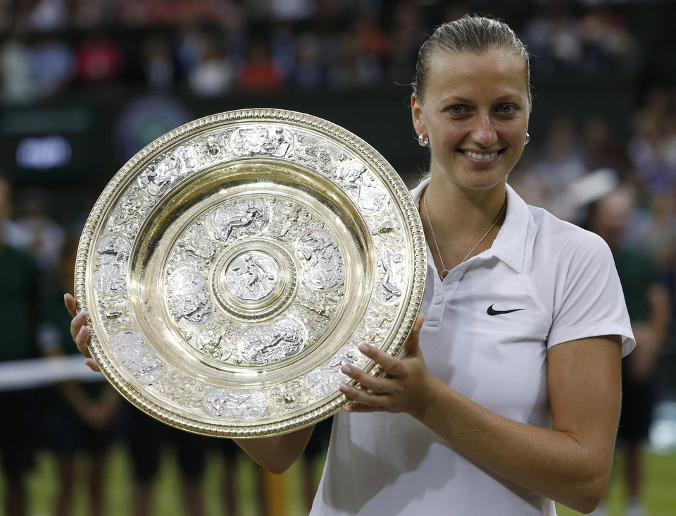 Photo - Petra Kvitova of Czech Republic holds the  trophy after winning the women's singles final against Eugenie Bouchard of Canada at the All England Lawn Tennis Championships in Wimbledon, London, Saturday, July 5, 2014. (AP Photo/Sang Tan)