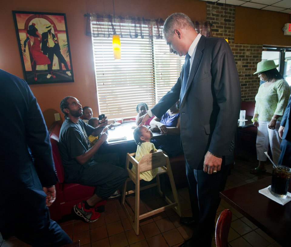 Photo - Attorney General Eric Holder touches the forehead of Yusayrah Jones, 2, has he arrives at Drake's Place Restaurant for a meeting with community leaders, Wednesday, Aug. 20, 2014 in Florrissant, Mo. Holder arrived in Missouri on Wednesday, a small group of protesters gathered outside the building where a grand jury could begin hearing evidence to determine whether a Ferguson police officer who shot 18-year-old Michael Brown should be charged in his death.   (AP Photo/Pablo Martinez Monsivais, Pool)