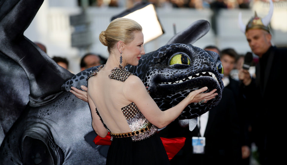 Photo - Actress Cate Blanchett touches a giant puppet of the dragon named Toothless during arrivals for the screening of How to Train Your Dragon 2 at the 67th international film festival, Cannes, southern France, Friday, May 16, 2014. (AP Photo/Alastair Grant)