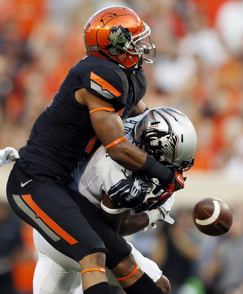 Photo - Oklahoma State's Ashton Lampkin (6) breaks up a pass intended for Texas Tech's Reginald Davis (2) in the first quarter during a college football game between the Oklahoma State Cowboys (OSU) and the Texas Tech Red Raiders at Boone Pickens Stadium in Stillwater, Okla., Thursday, Sept. 25, 2014. Photo by Nate Billings, The Oklahoman