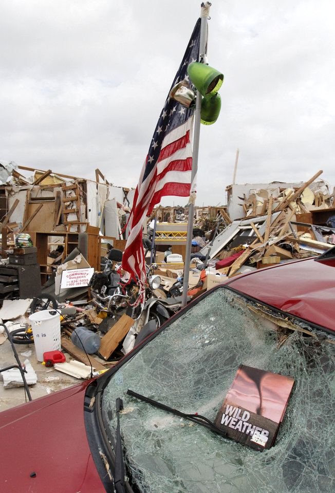 Photo - A survivor shows a sense of humor with a book found in the rubble of a home destroyed by the May 20th tornado near 145th and Robinson in Moore, OK, Saturday, May 25, 2013,  Photo by Paul Hellstern, The Oklahoman
