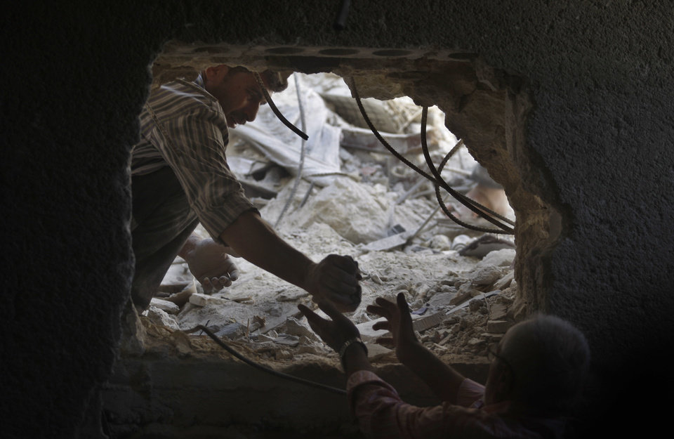 Photo -   Syrians look for the bodies two girls thought to be under the rubble of a building hit by a Syrian government airstrike in Aleppo, Syria, Sunday, Aug. 19, 2012 (AP Photo/ Khalil Hamra)