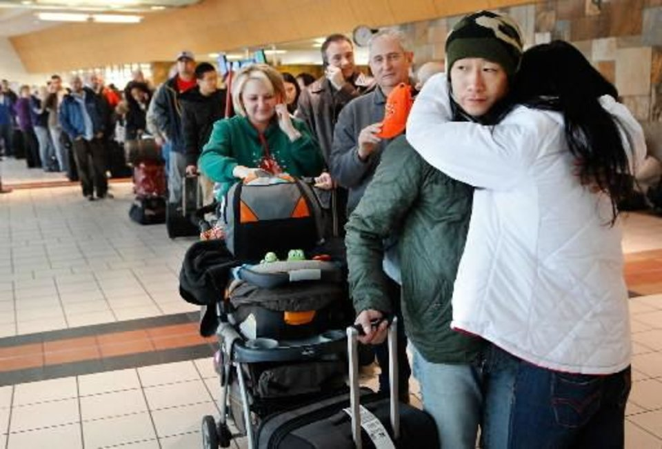Photo - Blizzard conditions in Oklahoma City Thursday, Dec. 24, 2009. Travelers at Will Rogers World Airport wait in long line to reschedule flights after announcement was made that all flights were cancelled. Photo by Jim Beckel