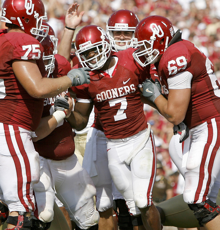 Photo - OU's DeMarco Murray celebrates with Tyler Evans, left, Landry Jones, and Eric Mensik after a touchdown during the first half of the college football game between the University of Oklahoma Sooners (OU) and Florida State University Seminoles (FSU) at the Gaylord Family-Oklahoma Memorial Stadium on Saturday, Sept. 11, 2010, in Norman, Okla.   Photo by Bryan Terry, The Oklahoman