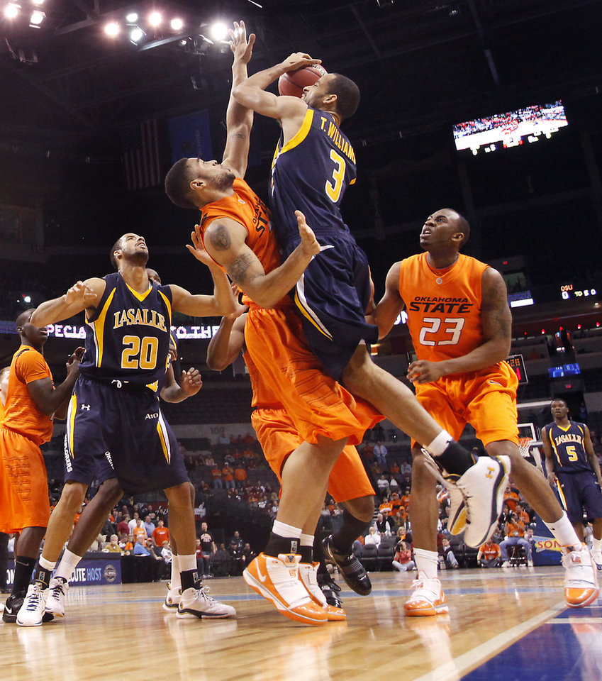 Photo - OSU's Marshall Moses (33) defends on La Salle's Terrell Williams (3) during the first half of the college basketball game between Oklahoma State University (OSU) and La Salle University in the All College Basketball Classic at the Ford Center on Monday, Dec. 21, 2009, in Oklahoma City, Okla.   Photo by Chris Landsberger, The Oklahoman ORG XMIT: KOD