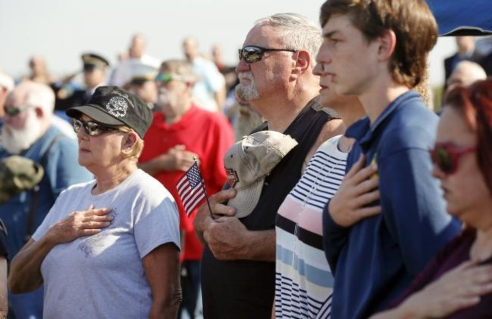 Photo -  Mourners stand for the national anthem during the funeral service for World War II veteran Herman White at Grace Hill Cemetery in Perry, Okla., Wednesday, Sept. 4, 2019. Hundreds of people attended Navy Seaman 2nd Class White's funeral after learning that he had no surviving family members to be there. [Nate Billings/The Oklahoman]
