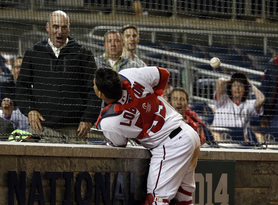 Photo - Washington Nationals catcher Jose Lobaton runs into the wall as he tries to catch a could ball by San Diego Padres' Tommy Medica during the 12th inning of a baseball game at Nationals Park on Thursday, April 24, 2014, in Washington. The Padres won 4-3 in 12 innings. (AP Photo/Alex Brandon)