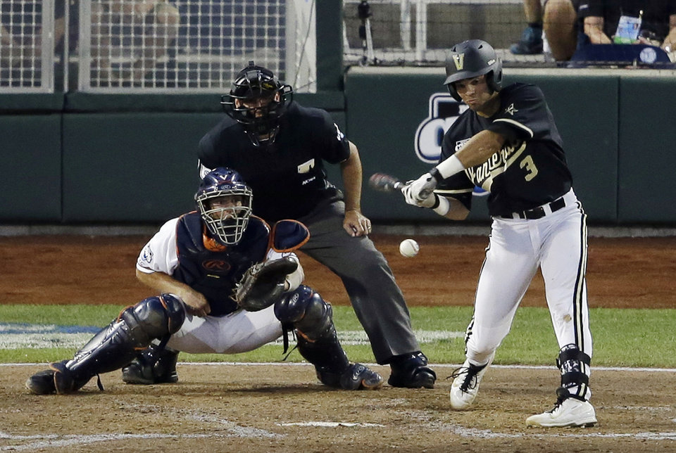Photo - Vanderbilt shortstop Vince Conde hits an RBI single against Virginia in the sixth inning of the last game of the best-of-three NCAA baseball College World Series finals, in Omaha, Neb., Wednesday, June 25, 2014. (AP Photo/Nati Harnik)