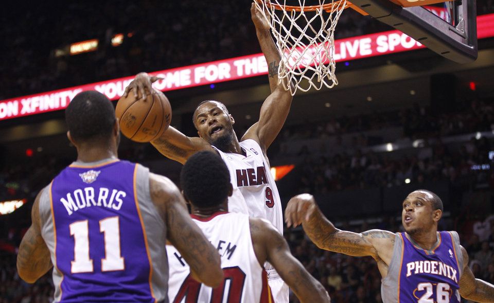 Miami Heat's Rashard Lewis (9) rebounds a ball as Udonis Haslem (40) defends Phoenix Suns' Markieff Morris (11) and Shannon Brown (26) during the first half of an NBA basketball game in Miami, Monday, Nov. 5, 2012. (AP Photo/J Pat Carter)