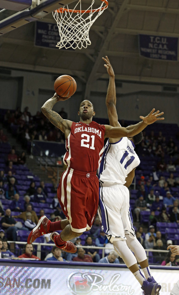 Photo - Oklahoma forward Cameron Clark looks for the basket as TCU forward Brandon Parish (11) defends in the first half of an NCAA basketball game Saturday, March 8, 2014, in Fort Worth, Texas. Oklahoma won 97-67. (AP Photo/Sharon Ellman)