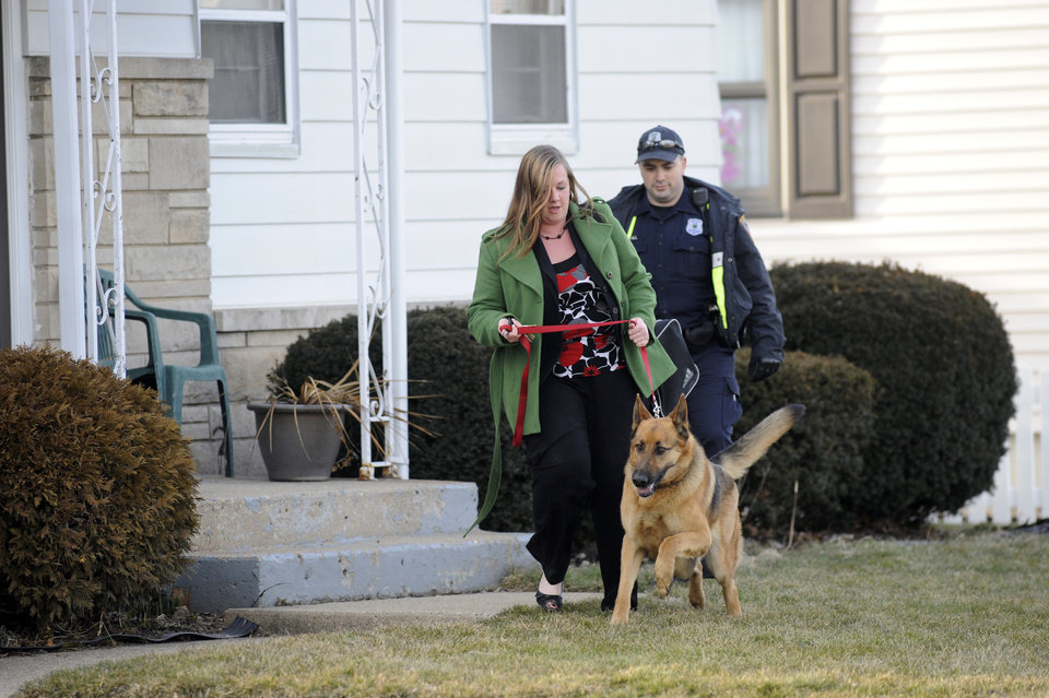South Bend police remove a resident from her home near the scene of a plane crash near the South Bend Regional Airport Sunday March 17, 2013 in South Bend, Ind. The private jet apparently experiencing mechanical trouble crashed Sunday in a northern Indiana neighborhood, resulting in injuries and striking three homes, authorities and witnesses said. (AP Photo/Joe Raymond) ORG XMIT: INJR103