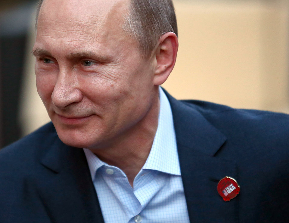 Photo - Russian President Vladimir Putin wears a Team USA pin while visiting USA House in the Olympic Village during the 2014 Winter Olympics on Friday, Feb. 14, 2014, in Sochi, Russia.  (AP Photo/Marianna Massey, USOC Pool)