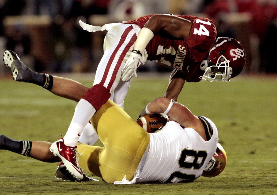 Oklahoma defensive back Aaron Colvin (14) tackles Notre Dame tight end Tyler Eifert (80) during the second half of the college football game where the University of Oklahoma Sooners (OU) were defeated by the Fighting Irish of Notre Dame (ND) 30-13 at Gaylord Family-Oklahoma Memorial Stadium in Norman, Okla., on Saturday, Oct. 27, 2012. Photo by Steve Sisney, The Oklahoman