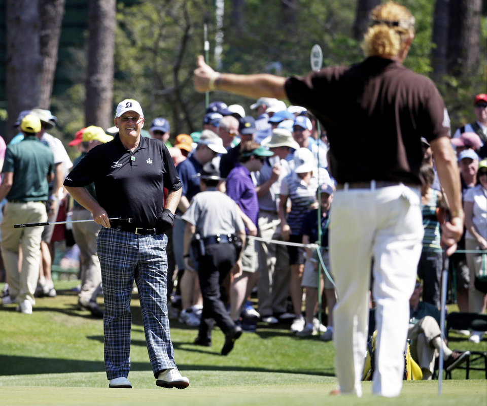 Photo - Miguel Angel Jimenez, right, of Spain, gives Sandy Lyle, of Scotland, a thumb's up after Lyle's birdie on the sixth green during the third round of the Masters golf tournament Saturday, April 12, 2014, in Augusta, Ga. (AP Photo/Darron Cummings)