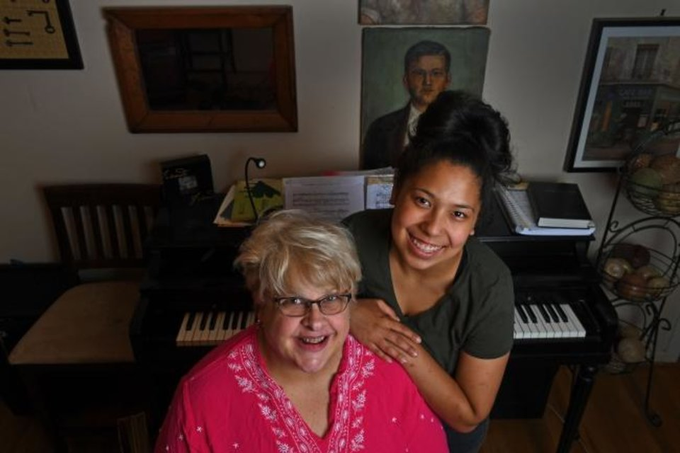 Photo -  Karen Yoho and daughter Mary Alyce Yoho, 17, in front of a piano found on Craigslist last year, on June 4 in Greenbelt, Maryland. It is the third piano they've acquired over the years. [Katherine Frey/Washington Post]