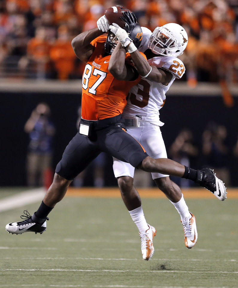 Photo - Oklahoma State's Tracy Moore (87) makes a catch as Texas' Carrington Byndom (23) during a college football game between Oklahoma State University (OSU) and the University of Texas (UT) at Boone Pickens Stadium in Stillwater, Okla., Saturday, Sept. 29, 2012. Texas on 41-36. Photo by Sarah Phipps, The Oklahoman