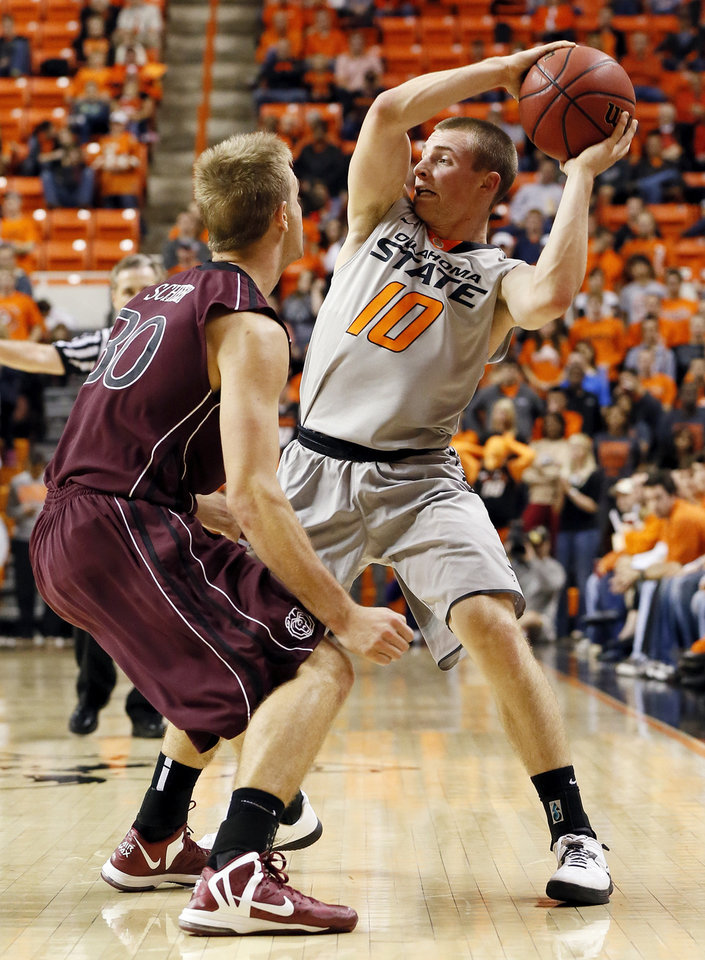 Photo - OSU's Phil Forte (10) looks to pass around around Nathan Scheer (30) of Missouri State during a men's college basketball between Oklahoma State University and Missouri State at Gallagher-Iba Arena in Stillwater, Okla., Saturday, Dec. 8, 2012. Photo by Nate Billings, The Oklahoman