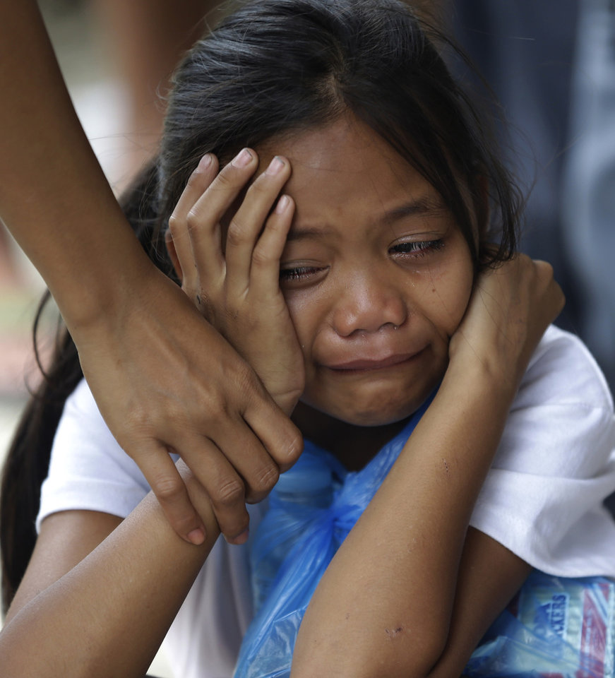 A girl is comforted upon seeing the sealed coffin of her relative at a damaged public market which now serves as a makeshift mortuary for typhoon Bopha's victims at New Bataan township, Compostela Valley in southern Philippines Saturday Dec. 8, 2012. Search and rescue operations following typhoon Bopha that killed nearly 600 people in the southern Philippines have been hampered in part because many residents of this ravaged farming community are too stunned to assist recovery efforts, an official said Saturday. (AP Photo/Bullit Marquez)