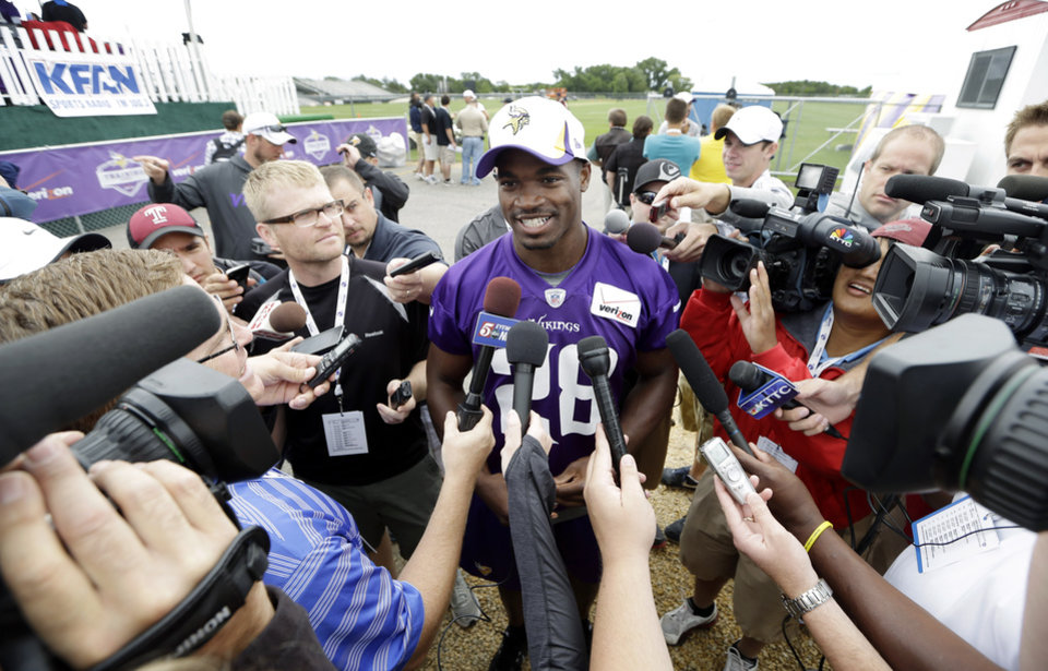Photo - Minnesota Vikings running back Adrian Peterson, center, speaks to the media following practice at NFL football training camp, Friday, July 26, 2013, in Mankato, Minn. (AP Photo/Charlie Neibergall)