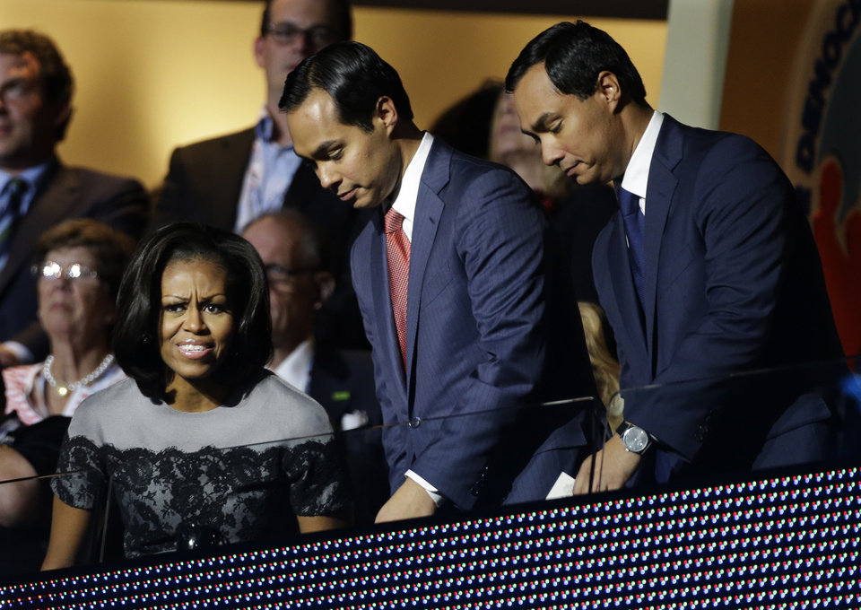 Photo - First lady Michelle Obama sits with San Antonio Mayor Julian Castro and his brother Joaquin Castro, center, at the Democratic National Convention in Charlotte, N.C., on Wednesday, Sept. 5, 2012. (AP Photo/Charlie Neibergall)  ORG XMIT: DNC184